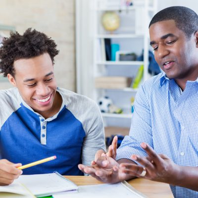 Mid adult African American dad helps teenage sone with homework assignment. The dad gestures while explaining something to his son.